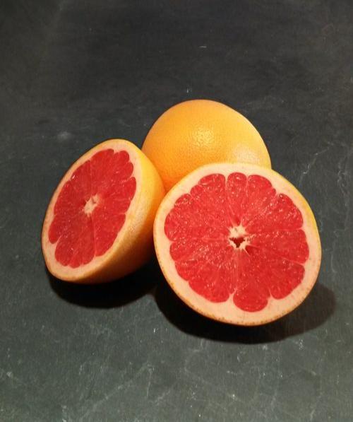 Foto einer aufgeschnittenen und einer ganzen Pink Grapefruit